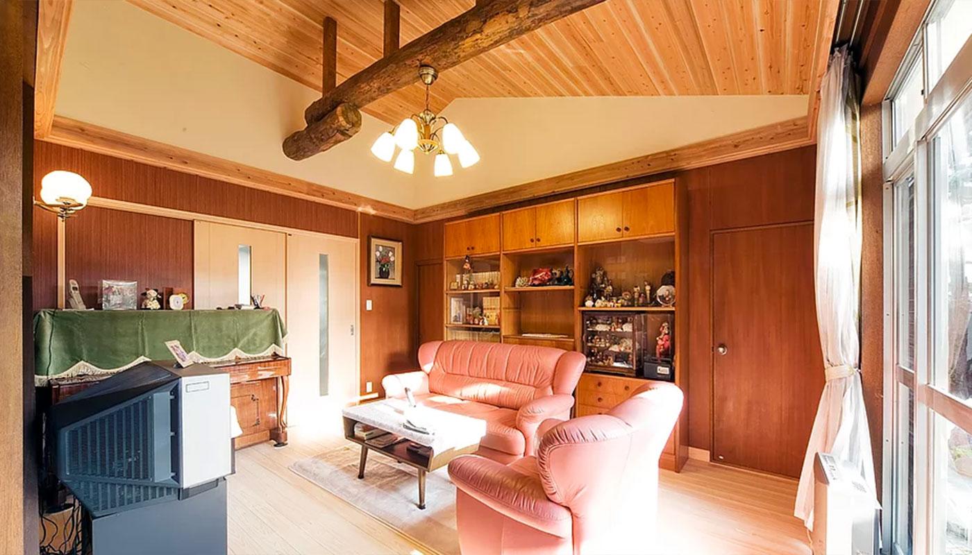 既存の丸太梁をみせた勾配天井のあるリビング